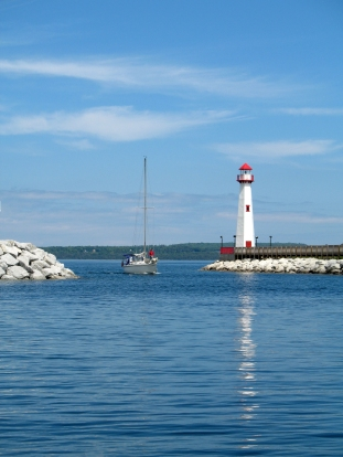 A sailboat enters the St. Ignace harbor with Mackinac Island in the distance beyond.